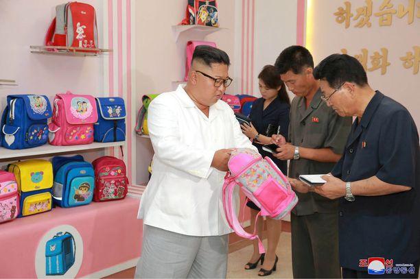 Pohjois-Korean johtaja hypisteli lasten reppuja tehtaassa Wonsanissa.