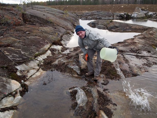 Juha Natunen testaa, ovatko kallioiden välissä olevat vesialtaat lähteitä vai eivät.