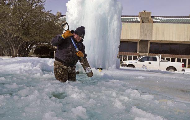 Richardsonin kaupungin työntekijä rikkoo jäätä jäätyneestä suihkulähteestä.
