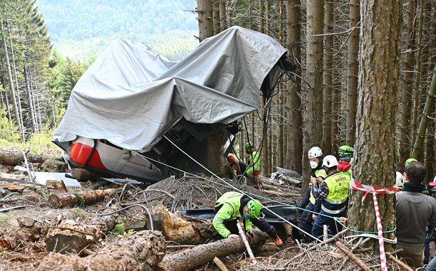 Murskaantunut köysiradan vaunu on peitetty pressulla Mottarone-vuoren rinteellä.