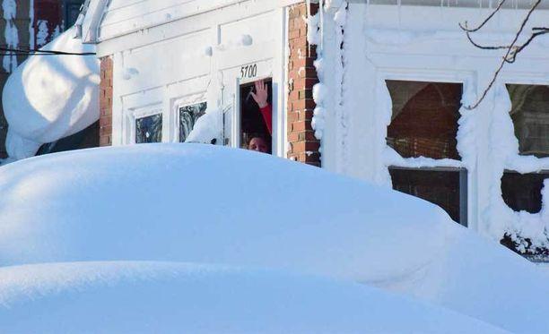 Nainen vilkutteli kotitalonsa ikkunasta herättyään yön lumimyrskyn jälkeen.