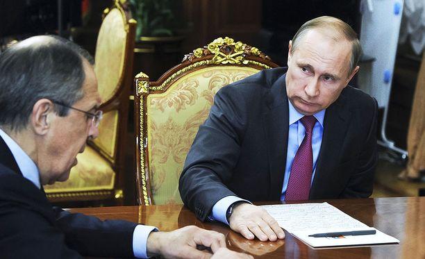 Tässä Putinin työhuoneessa pidetyssä tapaamisessa päätettiin joukkojen vetämisestä Syyriasta. Putinin taustalla näkyvää esinettä on luultu silityslaudaksi.