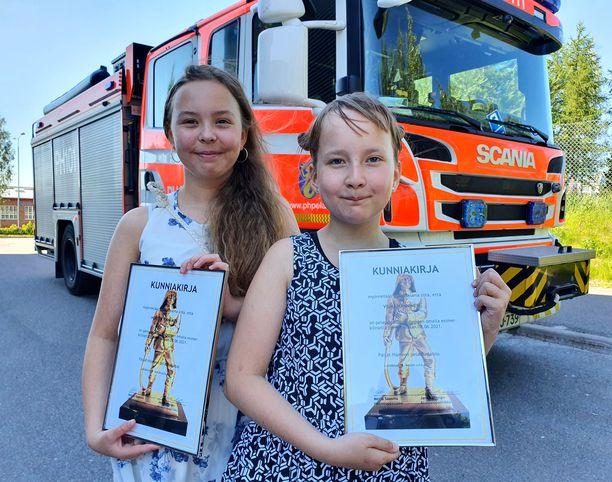 Päijät-Hämeen pelastuslaitos palkitsi Vilman (oik.) ja Hertan esimerkillisestä ja urhoollisesta toiminnasta.