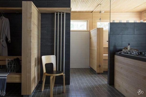 Miten raikas ja yhtä aikaa klassinen yhdistelmä! Vaakasuuntaan ladotut vaaleat sormipaneelit, tummat ja valkoiset laatat ja lasiseinät tuovat kylpylämäistä tunnelmaa kodin saunaosastolle. Huomaa, että myös poreamme on paneloitu.