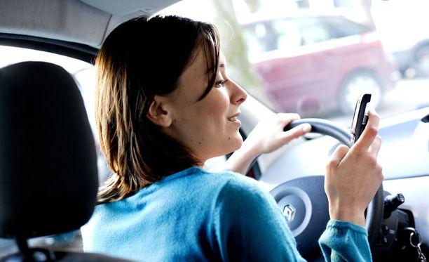 Ei näin. Kännykän räpeltäminen autoillessa on merkittävä riski liikenteessä. Kuvituskuva.