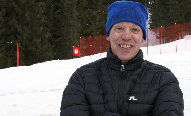 Jari Isometsä nauttii työstään MTV:n hiihtokommentaattorina. Kuvassa mies poseeraa Tour de Skin loppunousun Alpe Cermisin päällä keskellä laskettelurinnettä.