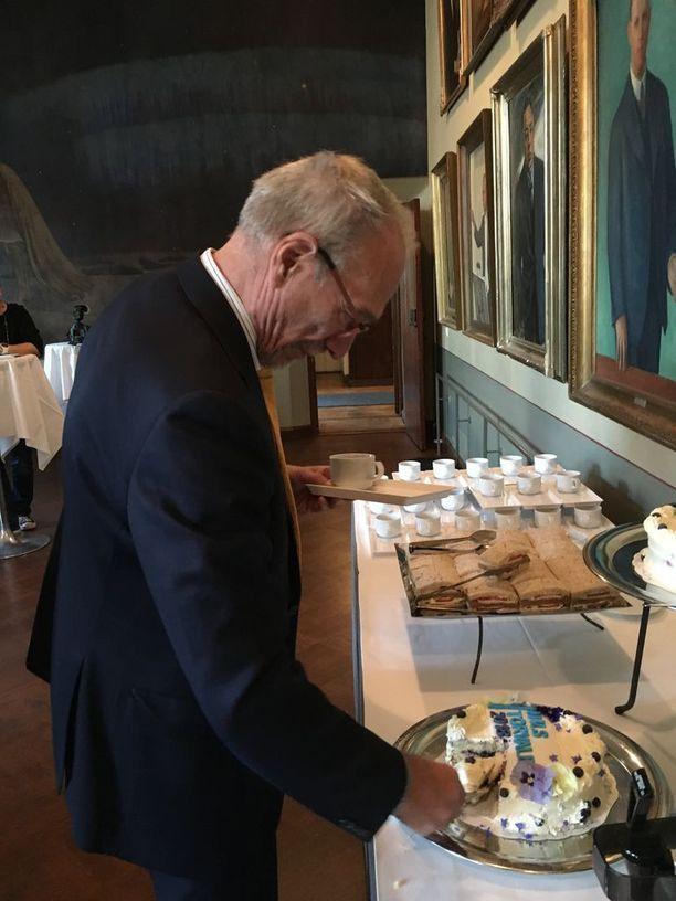 """Nils Torvalds otti palasen kakkua Helsingin Vanhalla ylioppilastalolla ennen tiedotustilaisuutensa alkamista. Kakussa luki """"Nils Torvalds 2018""""."""