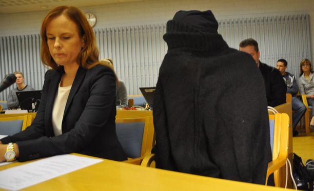 Syytetty saapui oikeudenkäyntiin mustaan neuleeseen verhoutuneena.