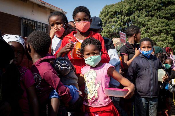 Ihmiset jonottavat saadakseen ilmaista ruokaa Etelä-Afrikan Johannesburgissa 18. heinäkuuta. Monen ruokaturva on heikentynyt entisestään koronapandemian seurauksena.