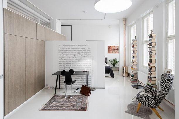 Työpisteen ja makuuhuoneen erottaa tosistaan seinäke, jota vasten työpöytäkin on sijoitettu. Hauskat kirjahyllyt sopivat molempien tilojen tunnelmaan.