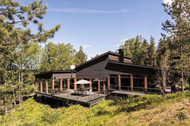 Tämä moderni puutalo sijaitsee metsätontilla luonnon keskellä.