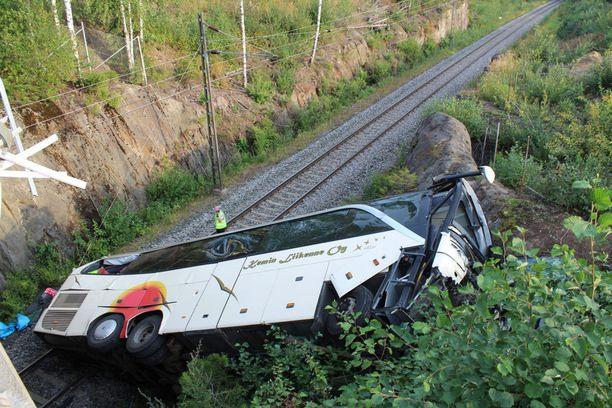 Linja-auton vääntyneet rakenteet kertoivat törmäyksen ja pudotuksen voimasta.