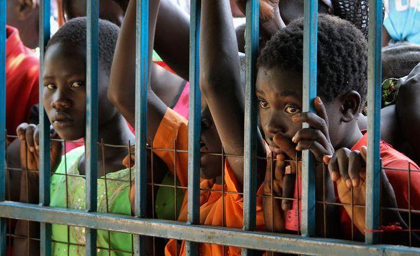 Lapset ja naiset jonottavat ruokaa, saippuaa ja vilttejä UNHCR:n avustuspisteellä Yein kaupungissa, joka on sisällissodan keskus.