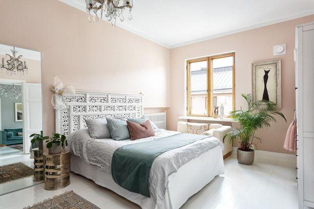 Roosat seinät, valkoiseksi maalatut lautalattiat ja suuri viherkasvi tuovat tähän huoneeseen seesteistä ja rauhallista tunnelmaa. Suuri peili taas tuo tilan tuntua.