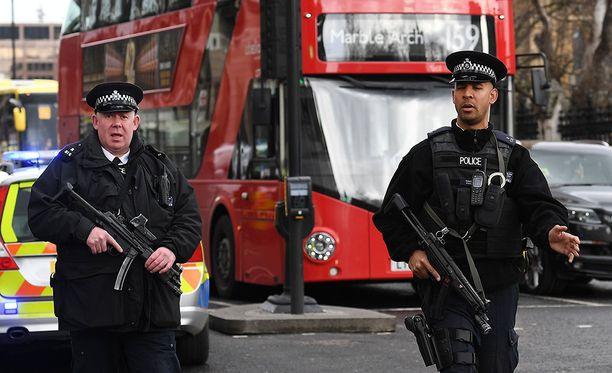 Poliisi partioi raskaasti aseistettuna Lontoossa.