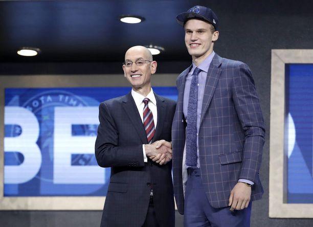 NBA-komissaari Adam Silver puristi tuoreen seiskavarauksen Lauri Markkasen kättä. Kuvan Minnesota-lippis vaihtui varsin pian Chicago Bullsin lätsään.