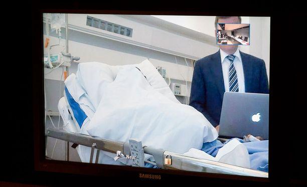 Epäilty osallistui vangitsemisoikeudenkäyntiin videokuvan välityksellä sairaalasta. Hän piiloutui kuvaajia tyynyn taa.