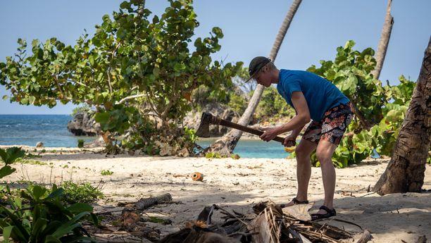 Helmeri antoi kirveelle kyytiä. Työkalua ei kuitenkaan tarvittu, kun lähimaastosta löytyi valmiiksi mittaan sahattuja puita majaa varten.