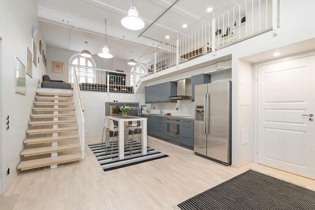 Suuret kattolamput sitovat hauskasti tämän loft-asunnon ylä- ja alakerran yhdeksi suureksi tilaksi.