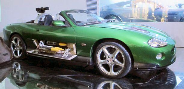 Tunnetusti Bondin autoissa piilee yllätyksiä, kuten tämän Jaguar XKR:n kyljistä esiin nousevat raketit. Elokuva oli Kuolema saa odottaa ja vuosi 2002.