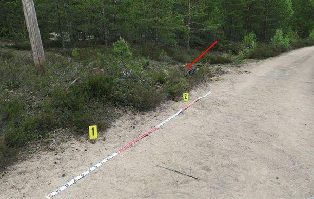 Ruumis löytyi nuolen osoittamasta paikasta. Keltaiset numerokyltit osoittavat hylsyjen löytöpaikkaa.