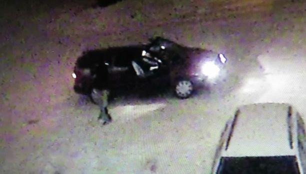Poliisin julkaisema valvontakameran kuva vastaanottokeskuksella käyneestä tummasta autosta ja autosta nousseesta henkilöstä.