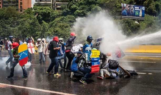 Mellakkapoliisit ampuvat mielenosoittajia vesitykeillä ja kyynelkaasulla.