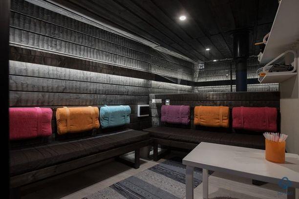 Rohkeasti väriä! Saunan ja tuvan välillä on lasiseinä. Valaistus on tunnelmallinen ja värejä on käytetty hauskasti.