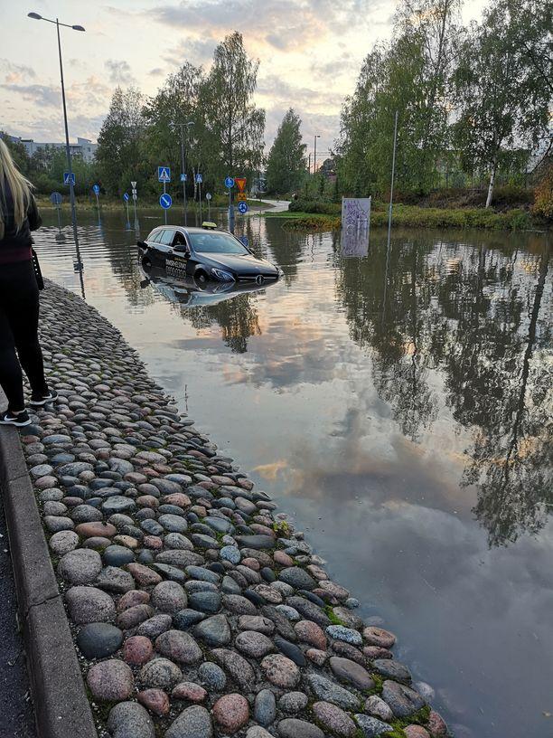Taksi joutui kiipeliin veden valtaamalla kadulla.