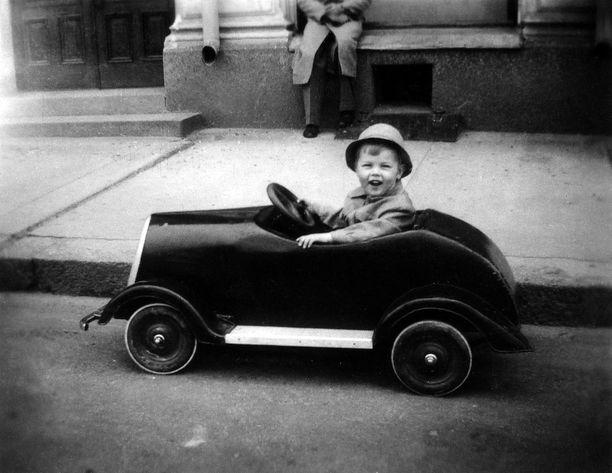 Pieni Ilkka-poika iloisena polkuautossaan.