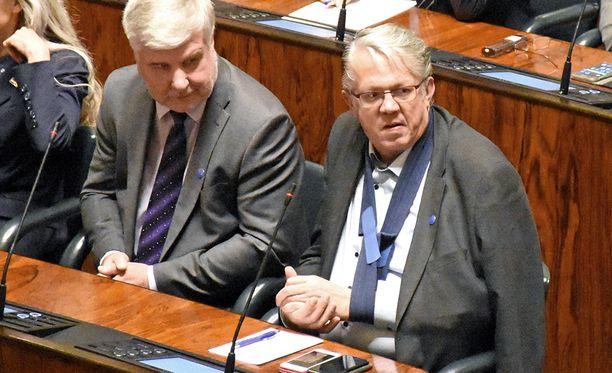 Ex-ministeri Juha Rehula (kesk) kuunteli käsi paketissa eduskunnan kyselytuntia torstaina.