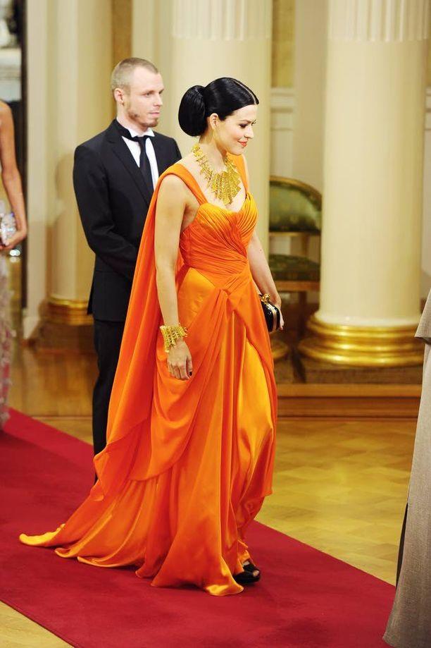 Jenni Vartiainen edusti vuonna 2010 Linnan juhlissa pirteän oranssissa iltapuvussa.