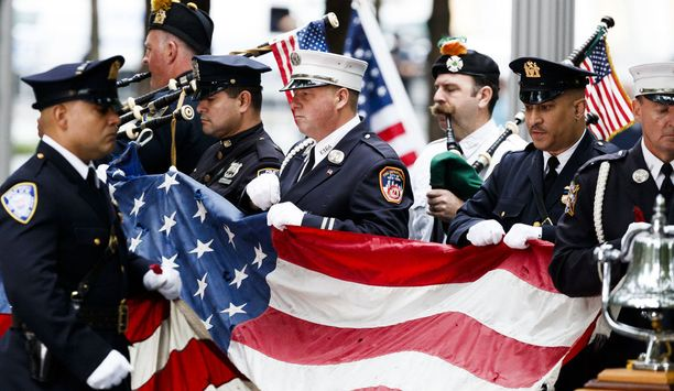 World Trade Centerin torneihin kohdistuneesta terrori-iskusta tulee kuluneeksi 17 vuotta 11.9.2018. Kuvassa Yhdysvaltain palomiehet ja poliisit kantavat tornissa liehunutta lippua iskun muistotilaisuudessa.