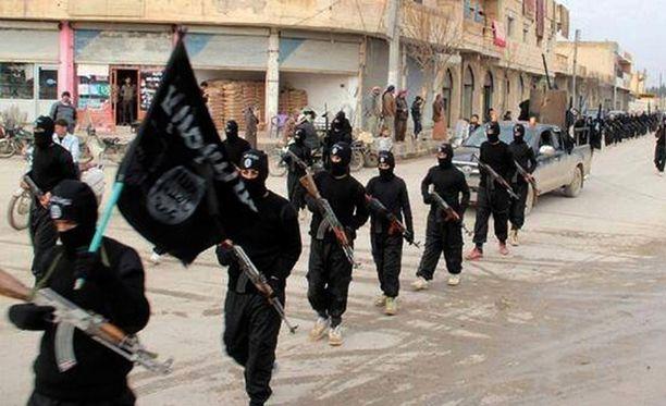 Tammikuussa 2014 julkaistussa, päiväämättömässä kuvassa Isisin lippua kantavat miehet marssivat Raqqassa, Syyriassa.
