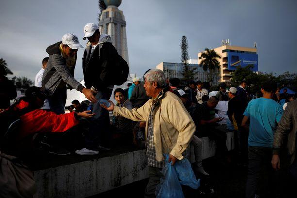 Vapaaehtoinen antaa vettä siirtolaiskaravaanissa odottavalle miehelle El Salvadorissa. Ryhmä lähti sunnuntaina kohti Yhdysvaltoja.