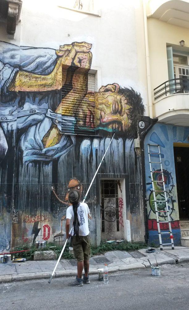 Vastapäätä Exarchian lukiota mies maalasi äänestyksen aikana jättimäistä graffitia seinään.