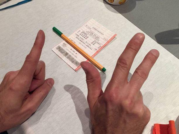 Kuvassa Eurojackpot-voittaja näyttää sormillaan noin 1,3 miljoonan euron voittosummaansa. Kahvittelupöydällä on myös voittajan pelitosite.