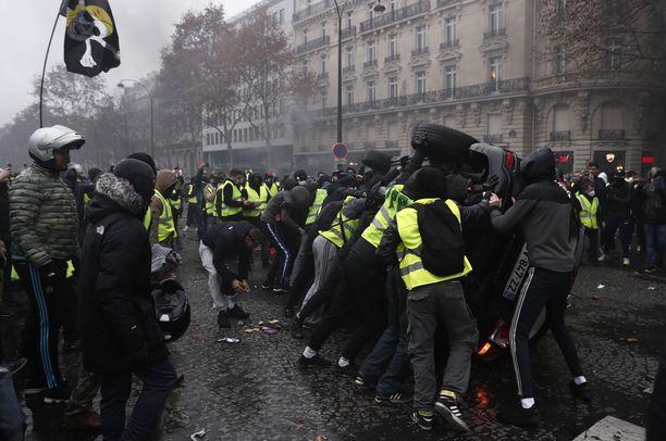 Mielenosoittajat käänsivät autoja katolleen Pariisissa lauantaina.