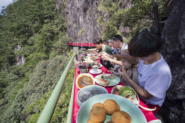 People have lunch on a footpath built on the cliff in Longquan Mountains in Longquan in east China's Zhejiang province Wednesday, Sept. 19, 2018, the first day the restaurant on the cliff.PHOTOGRAPH BY Feature China / Barcroft Images All Over Press