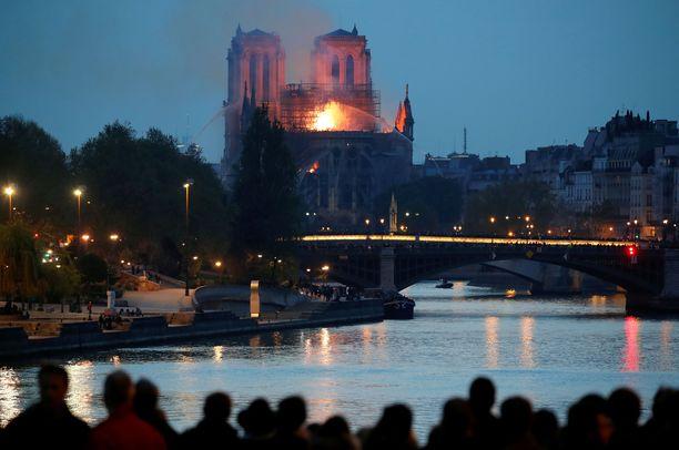 Taistelu liekkejä vastaan jatkuu Pariisin pimenevässä illassa.