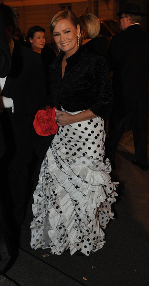 Musta-valkopilkullinen röyhelöhelmainen iltapuku sai väriläiskäkseen tulipunaista ruusua muistuttavan iltalaukun.
