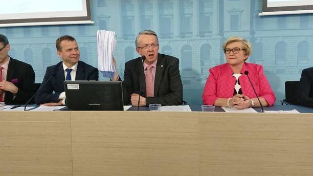 Perhe- ja peruspalveluministeri Juha Rehula esitteli 600-sivuista lakiluonnospinoa koskien sote- ja maakuntauudistuksia. Vasemmalla valtiovarainministeri Petteri Orpo ja oikealla kunta- ja uudistusministeri Anu Vehviläinen.