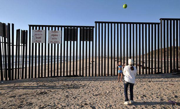 Äiti ja tytär pelaavat palloa nykyisen raja-aidan katveessa Tijuanassa.