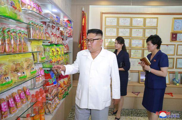 Kim Jong Un ja hänen vaimonsa Ri Sol Ju arvioivat erilaisia tuotteita makeistehtaalla.