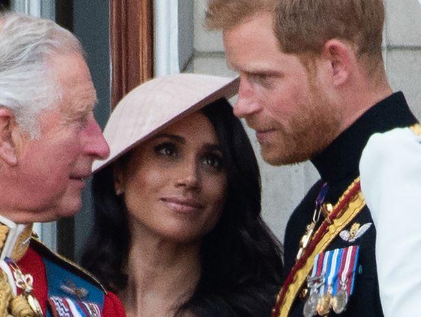 Vasemmalla prinssi Wales, keskellä herttuatar Meghan ja oikealla prinssi Harry.
