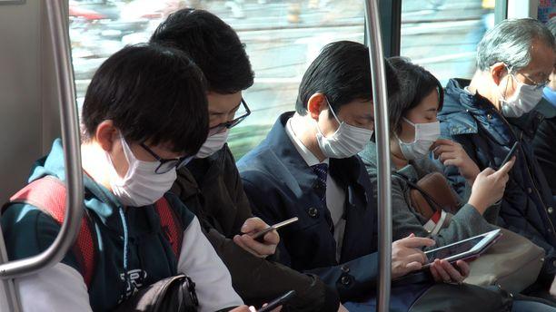 Linja-auton matkustajilla Tokiossa on suojanaamarit päällä.