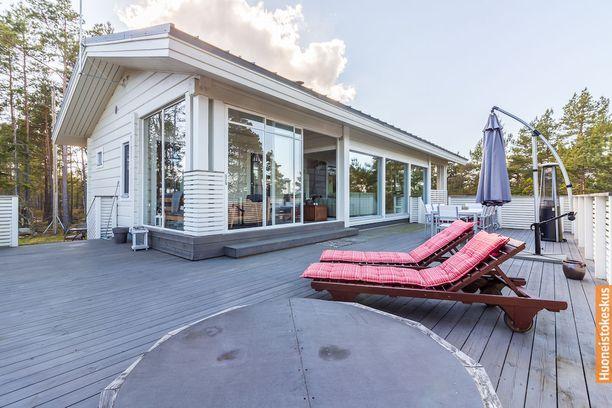 Tämä vuonna 2011 valmistunut talo Paraisen Nauvolla sijaitsee metsäisellä rinnetontilla meren rannassa.