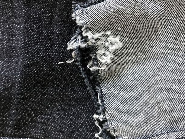 Kulutus polyesteria ja elastaania sisältävässä farkkukankaassa.