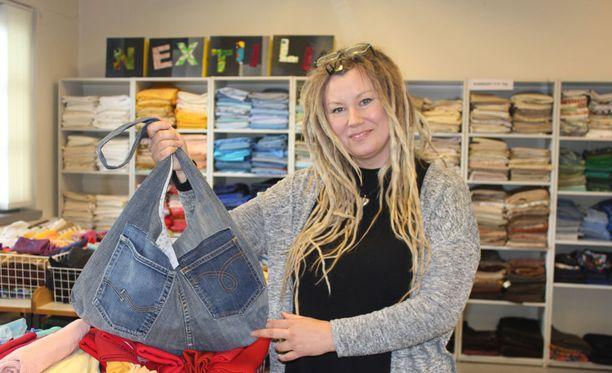 Työnohjaaja Katariina Helander kertoo kierrätysmateriaaleista syntyvän muun muassa monenlaisia vaatteita sekä farkkukasseja.