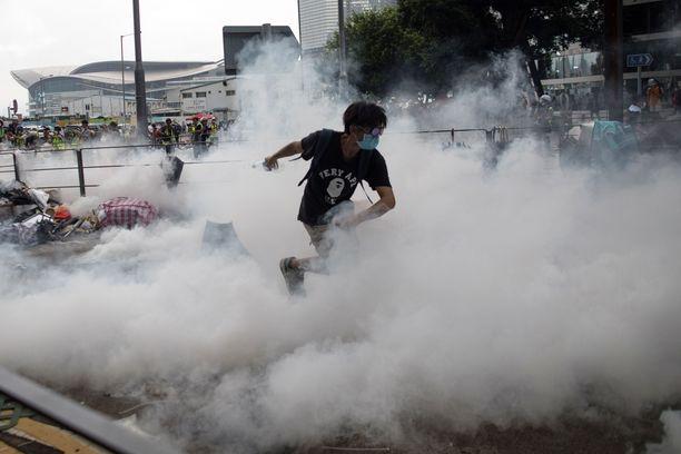 Mielenosoittaja juoksee poliisin heittämän kyynelkaasukranaatin aiheuttamassa savupilvessä.